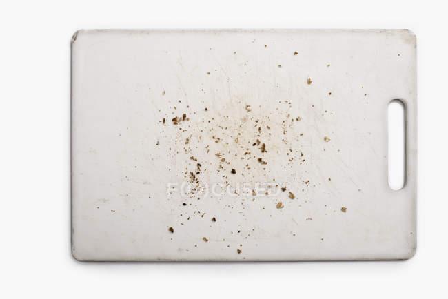Placa de corte de silício usada com migalhas e marcas de faca em fundo branco — Fotografia de Stock