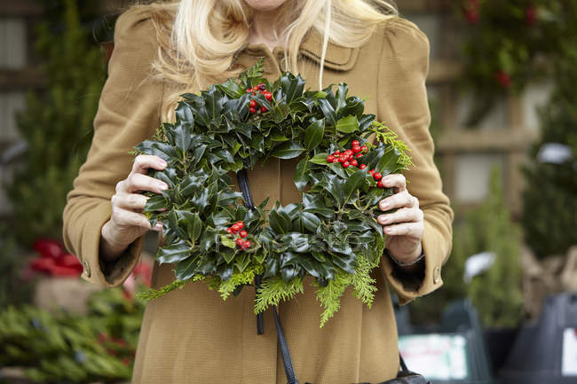 Cropped view of woman carrying decorated wreath of holly and evergreen leaves. — Stock Photo