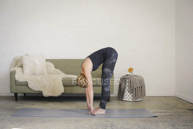 Blonde woman bending forwards on yoga mat in home interior. — Stock Photo