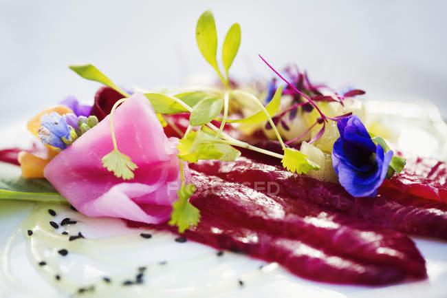 Карпаччо из и гарниром из свежего гороха побегов и съедобные цветы на белом фоне. — стоковое фото
