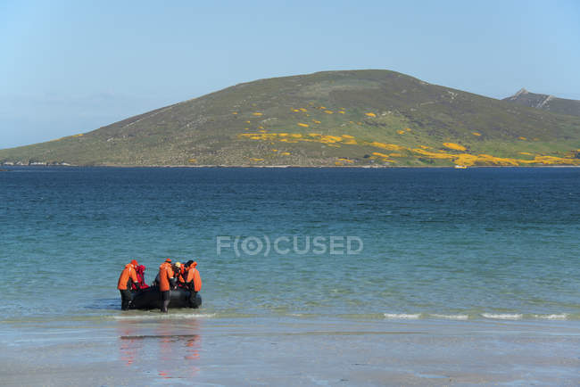 Group of people in rubber boat landing on beach on Falkland Islands. — Stock Photo