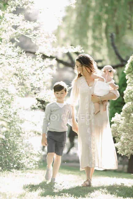 Mulher adulta meada com filho e filha caminhando no jardim. — Fotografia de Stock