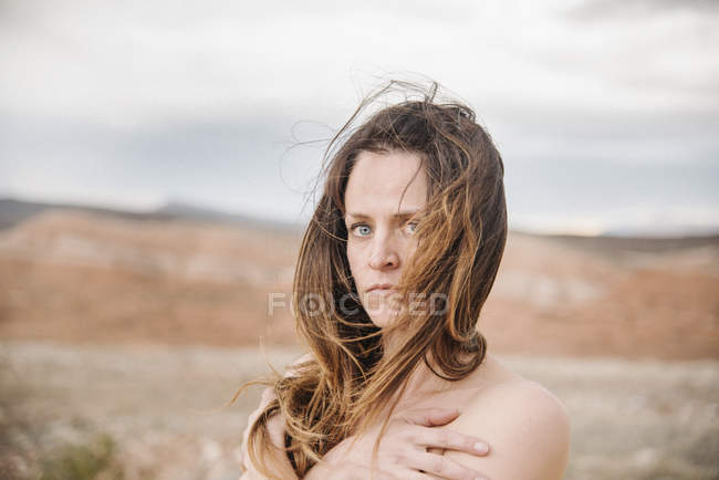 Woman with long brown hair standing in desert landscape. — Stock Photo