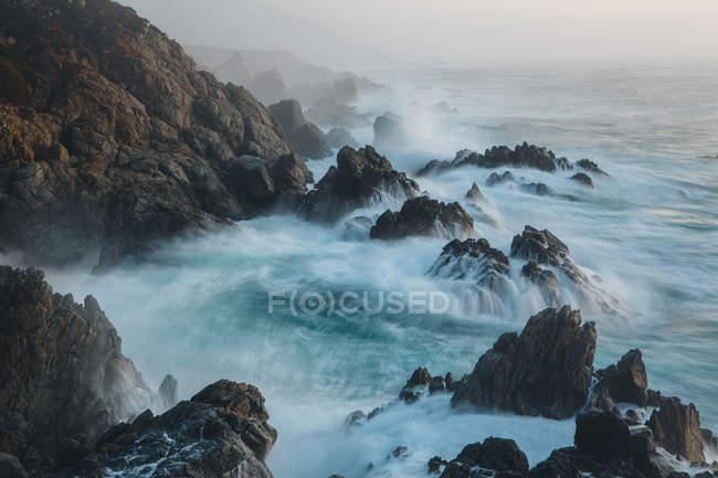 Хвилі і гуркотом проти скелястий берег на узбережжі Тихого океану. — стокове фото