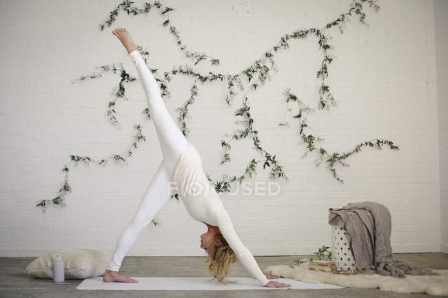 Blonde woman on white yoga mat bending down with leg raised. — Stock Photo