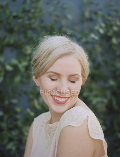 Portrait of woman in cream lace dress smiling with eyes closed. — Stock Photo