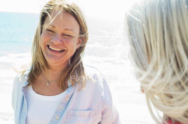 Усміхаючись блондинка літні жінки стоять океану з другом. — стокове фото