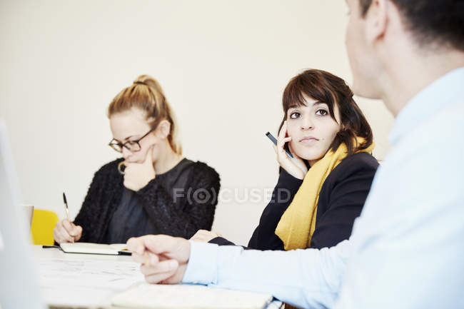 Coworkers sitting at business meeting around table. — Stock Photo