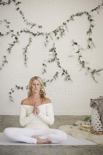 Blondine sitzt auf weißer Yogamatte in Lotusposition mit gefalteten Händen. — Stockfoto