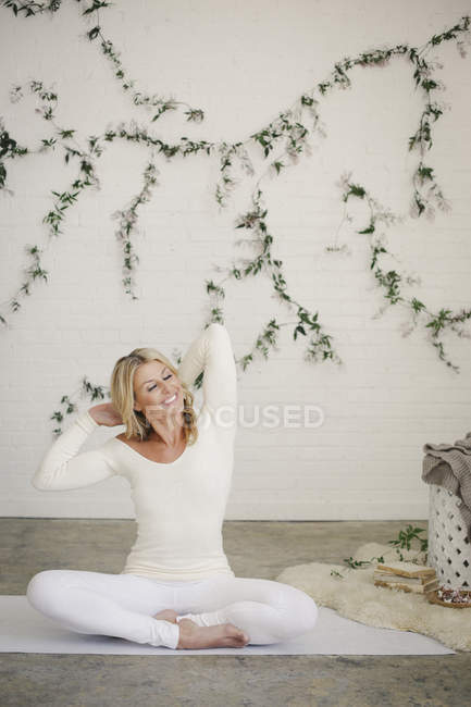 Smiling woman sitting on white yoga mat and stretching arms. — Stockfoto