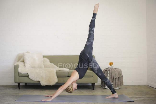 Blonde woman on yoga mat bending down with leg raised. — Stock Photo