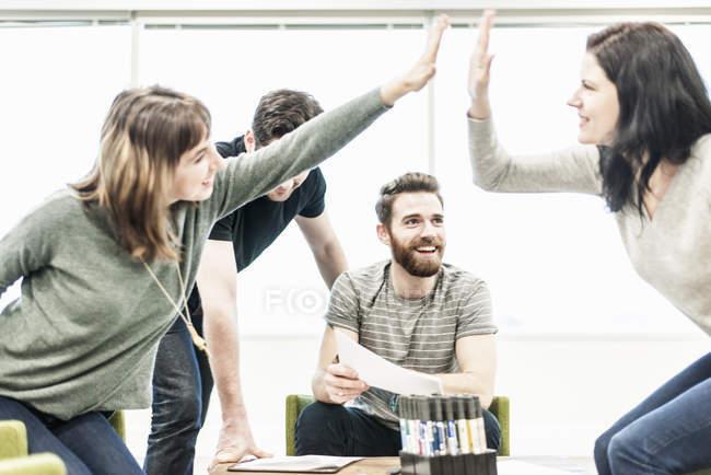 Женщины-коллеги на совещании по планированию дают пять . — стоковое фото