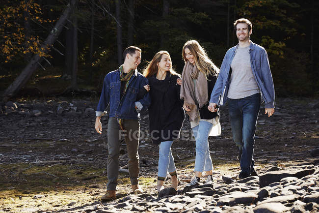 Couples walking hand in hand on sandy shore by forest. — Stock Photo