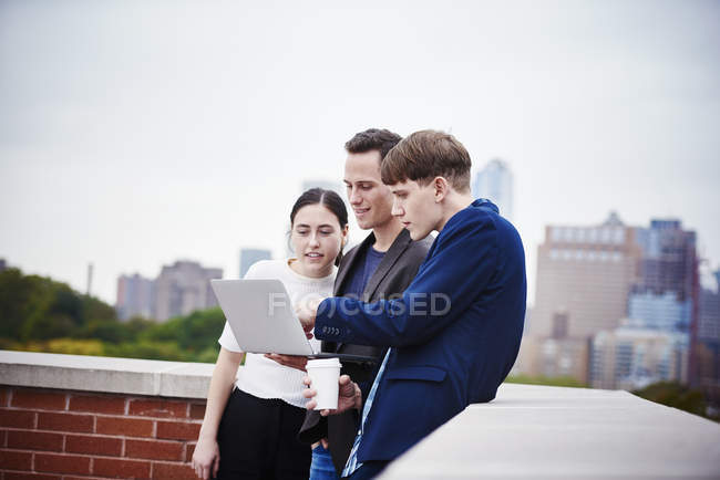 Young woman and men standing on rooftop and using laptop computer together. — Stock Photo