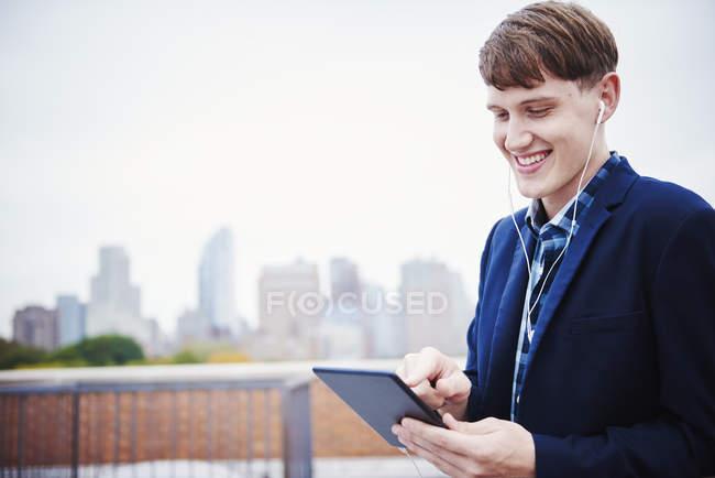 Giovane uomo in piedi sul tetto e guardando verso il basso tablet digitale . — Foto stock