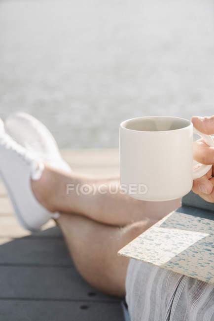 Человек, сидящий на пристани и держащий кружку и книгу на озере . — стоковое фото