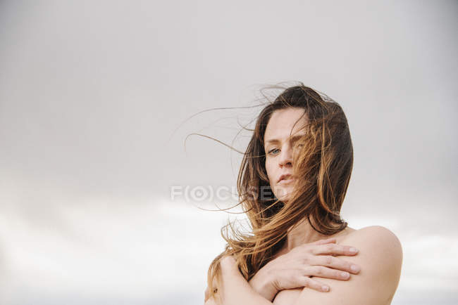 Woman with long brown hair standing against cloudy sky. — Stock Photo