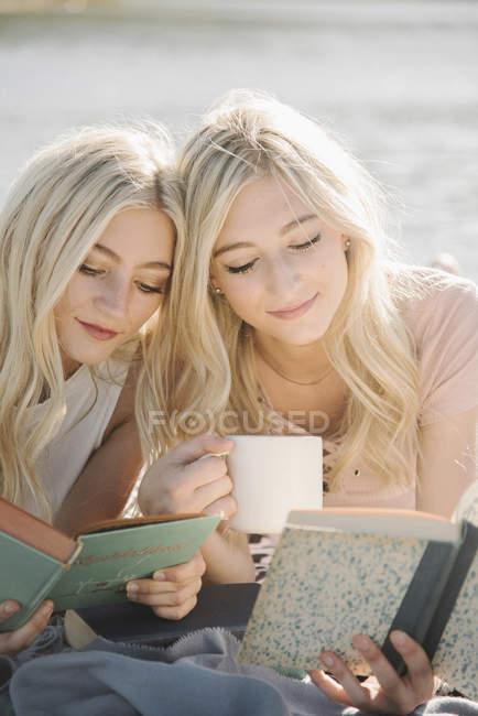 Dos hermanas adolescentes tumbadas en el embarcadero, leyendo libros y sosteniendo la taza . - foto de stock