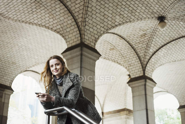 Woman with long hair holding smartphone and looking in camera under archway. — Stock Photo