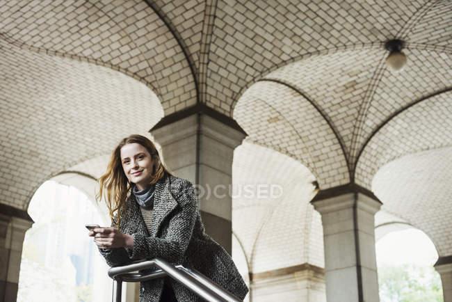 Femme aux cheveux longs tenant smartphone et regardant à la caméra sous l'arche . — Photo de stock