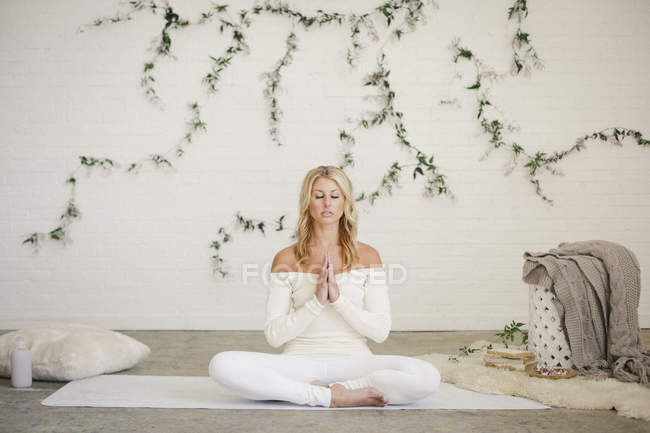 Blonde woman sitting on white yoga mat in lotus position with hands clasped. — Stock Photo