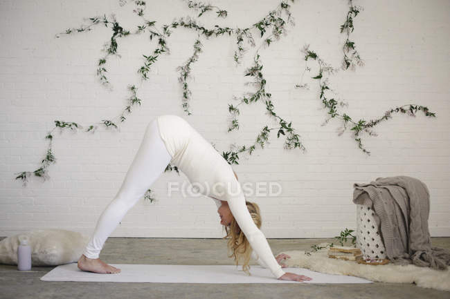 Blonde woman bending on yoga mat doing downward dog position. — Stock Photo