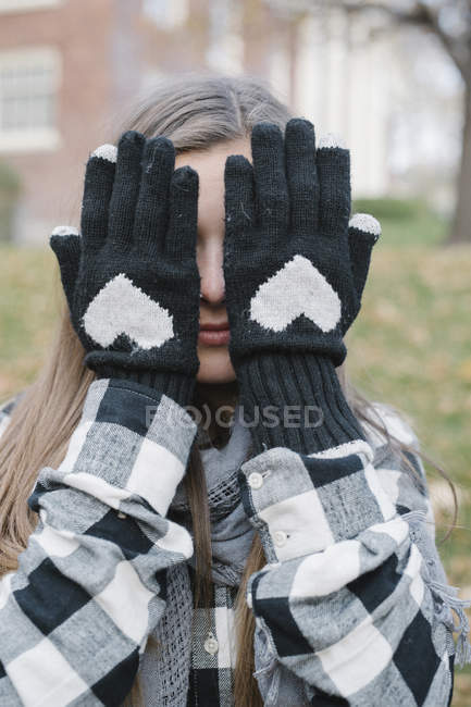 Young woman hiding face behind hands in woolly gloves with heart shaped design. — Stock Photo