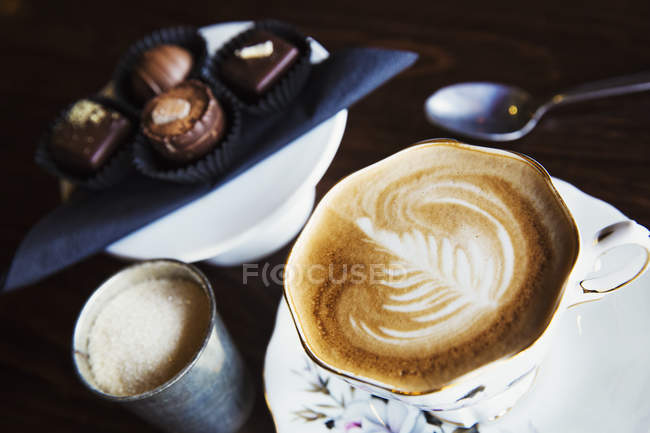 Assorted handmade chocolate candies on plate with cup of latte. — Stock Photo