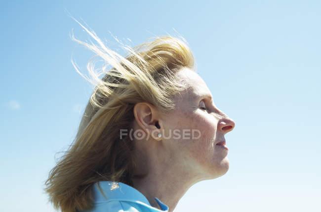 Profil de blonde femme mûre debout contre le ciel bleu . — Photo de stock