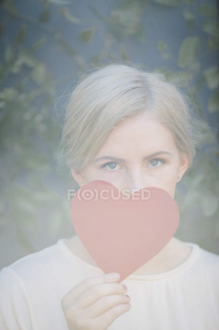 Portrait of woman holding red heart shape in front of face. — Stock Photo