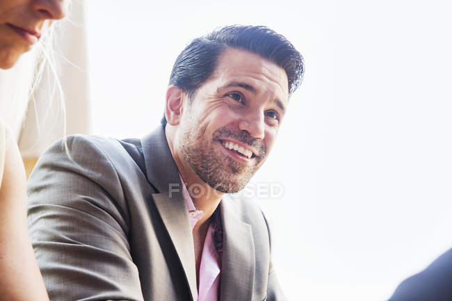 Smiling businessman in grey suit and pink shirt smiling and looking away. — Stock Photo