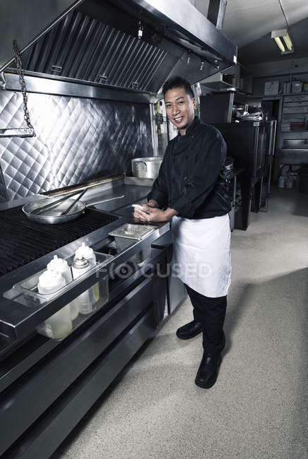 Male cook holding mobile phone in commercial restaurant kitchen. — Stock Photo