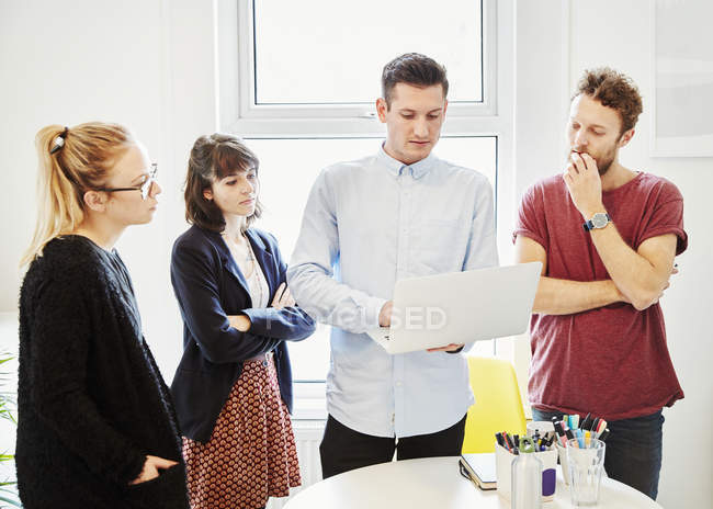 Coworkers standing around table at business meeting and looking at laptop. — Stock Photo