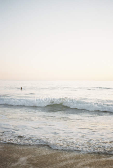 Ocean wave rolling onto sandy beach with person in background. — Stock Photo
