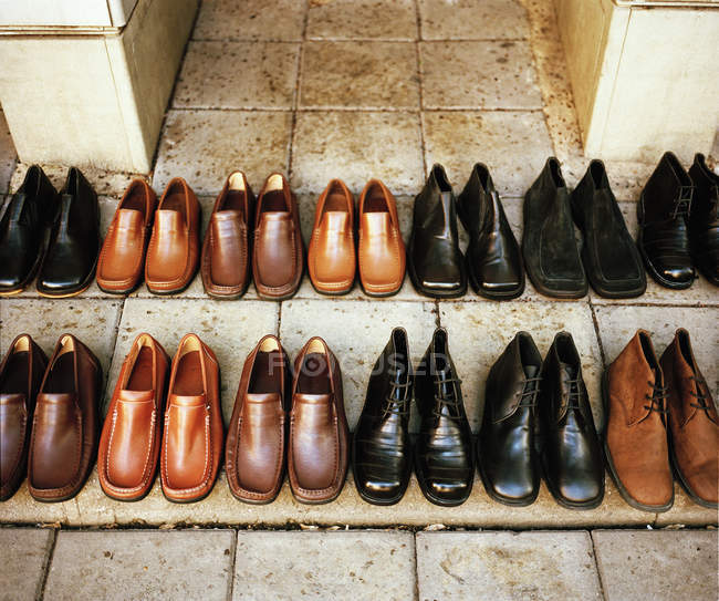 Rows of black and brown leather shoes on front steps of building. — Stock Photo