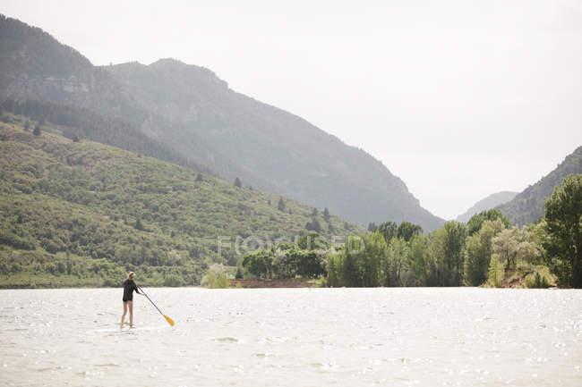Дівчинка-підліток встати з веслом серфінгу на гірському озері. — стокове фото