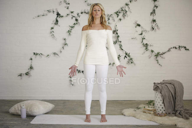 Blonde woman in a white leotard and leggings standing on white mat in room. — Stock Photo