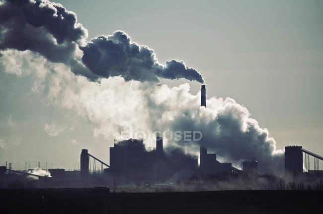 Calor, vapor e fumaça saindo das chaminés da usina contra o céu. — Fotografia de Stock