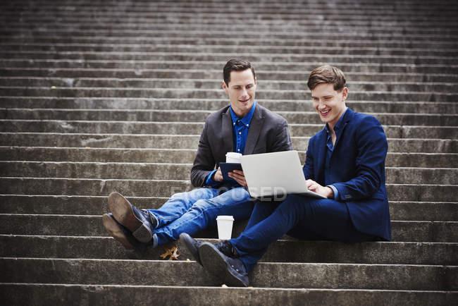 Dos jóvenes sentados en las escaleras de la ciudad y mirando juntos el portátil . - foto de stock