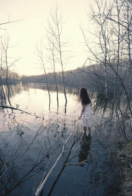 Mulher de vestido branco em pé em águas rasas ao entardecer pela margem do lago . — Fotografia de Stock