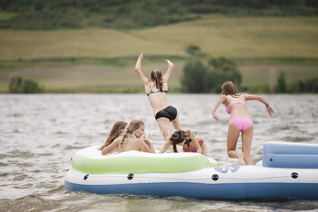 Teenage girls jumping and having fun on inflatable dinghy on lake. — Stock Photo