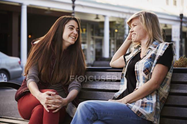 Zwei Frauen, die auf Bank in der Stadtstraße sitzen und reden. — Stockfoto