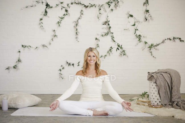 Blonde woman sitting on white yoga mat and meditating. — Stock Photo