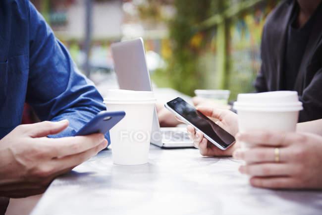 Primer plano de las manos de las personas que trabajan en la mesa con el portátil y los teléfonos inteligentes . - foto de stock