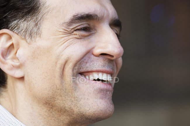 Uomo con i capelli grigi in camicia che distoglie lo sguardo e sorride . — Foto stock