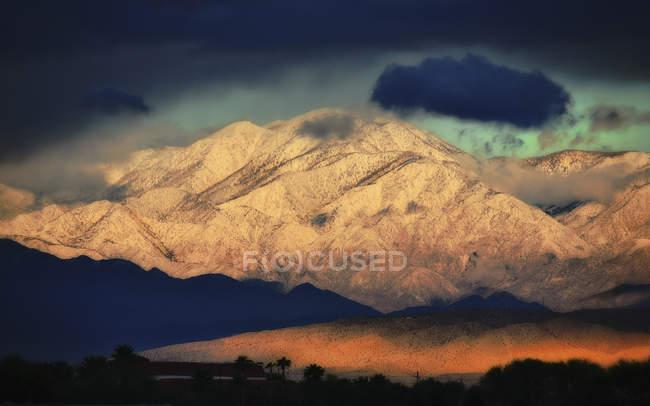 Verschneite Hänge des Gebirges mit dunklen Gewitterhimmel im Tal. — Stockfoto
