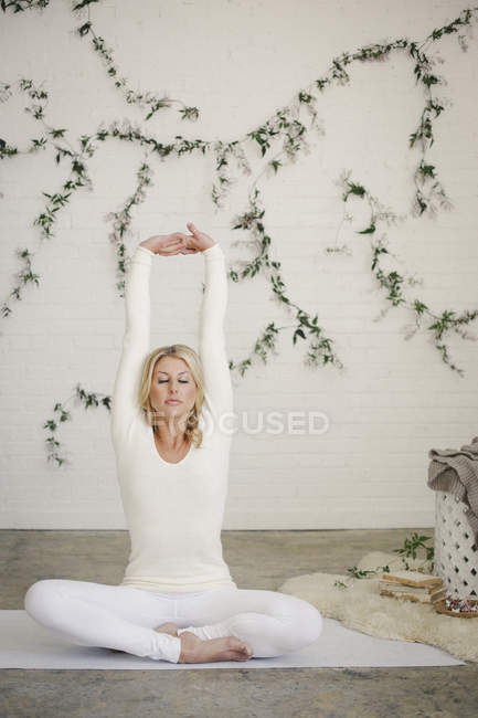 Mid adult woman in white leotard and leggings sitting on yoga mat and stretching arms. — Stock Photo