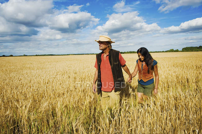 Man and woman holding hands while walking through field in summer. — Stock Photo
