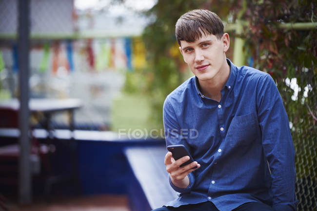 Young man sitting in city, holding smartphone and looking in camera. — Stock Photo