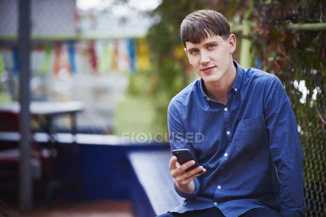 Jovem sentado na cidade, segurando smartphone e olhando para a câmera . — Fotografia de Stock